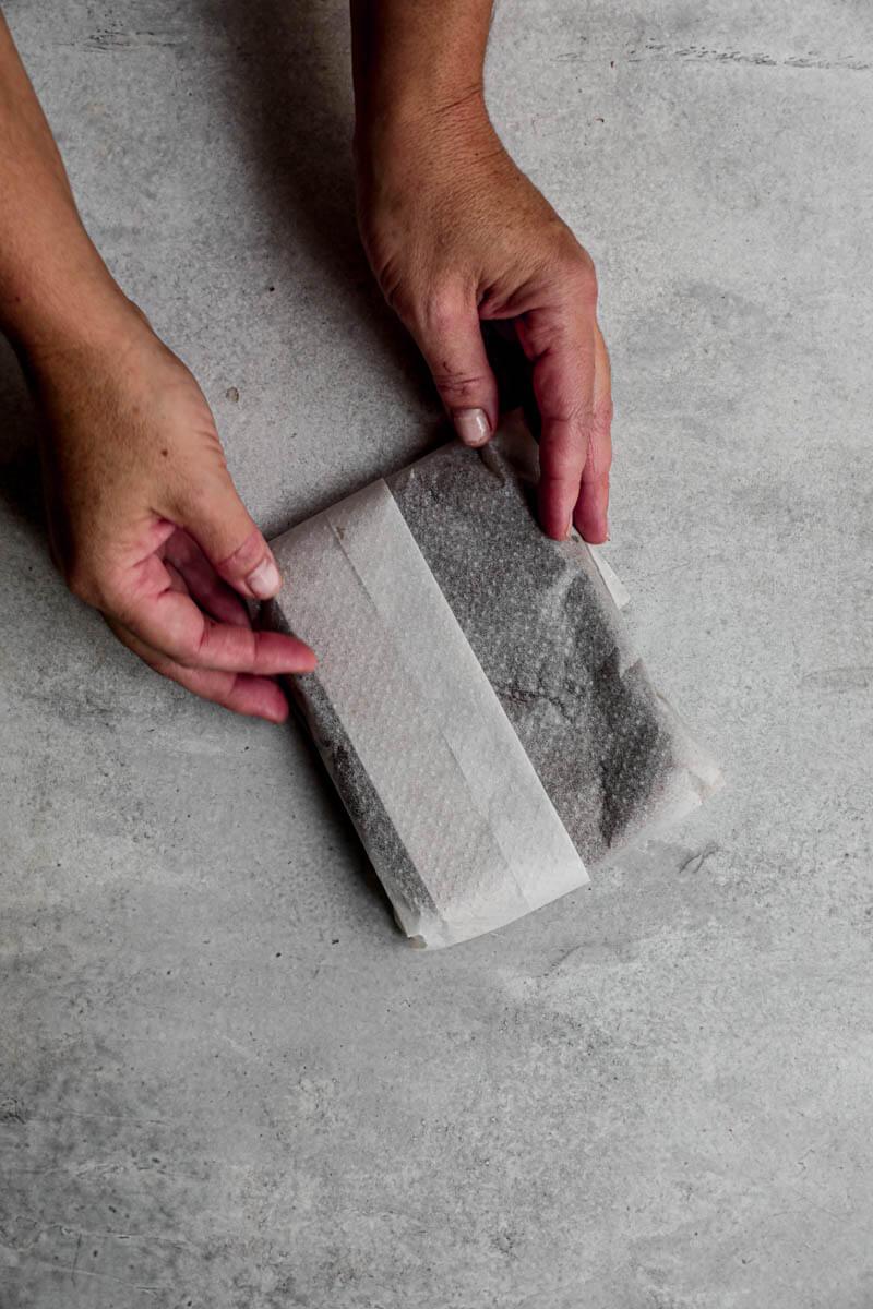 Plano aéreo de dos manos sosteniendo la masa de los alfajores envuelta en papel manteca