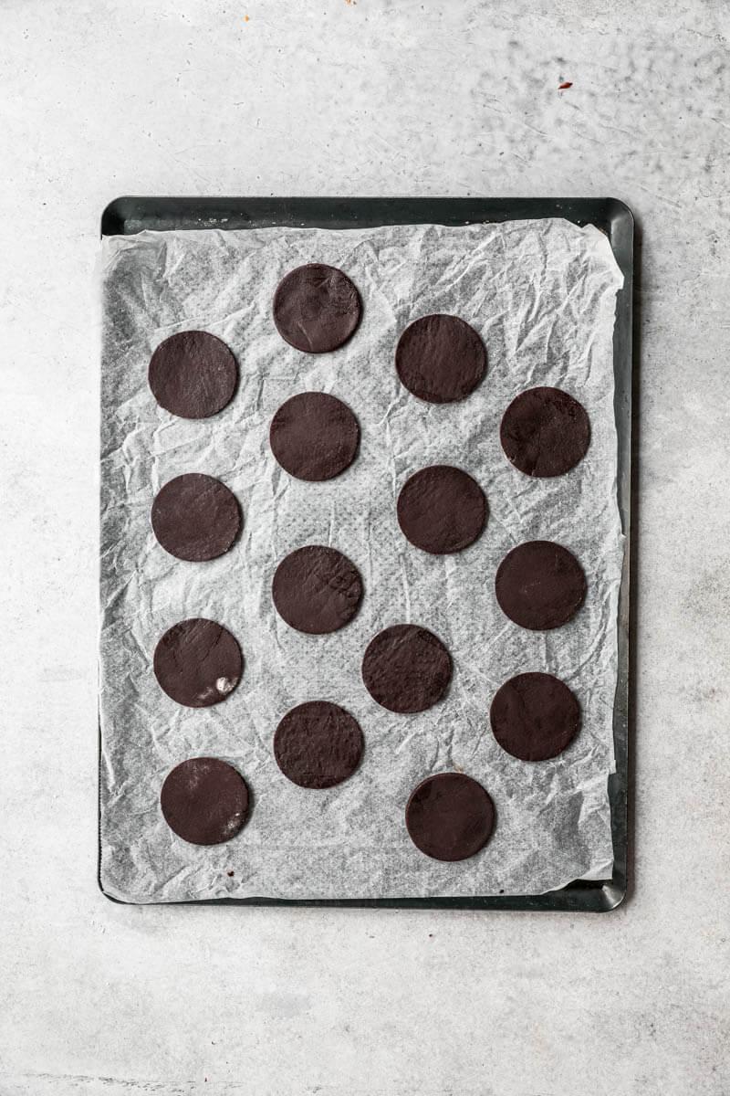Plano aéreo de las tapas de los alfajores de chocolate en una placa listas para el horno