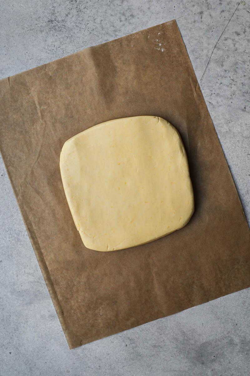 La masa de alfajores de maicena en forma de rectángulo sobre un trozo de papel vegetal marrón.