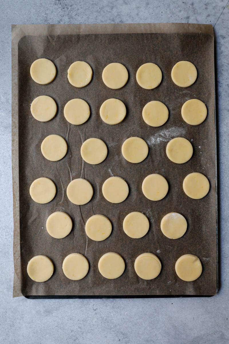 Las tapas de los alfajores de maicena sobre una bandeja forrada con papel manteca.