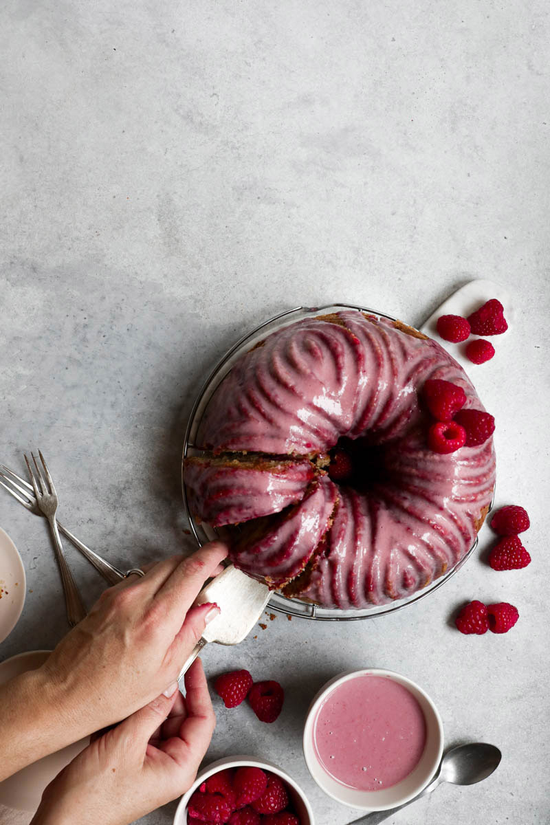 Bizcocho de chocolate blanco y frambuesa con glaseado rosa visto desde arriba. Con dos manos retirando una porción.