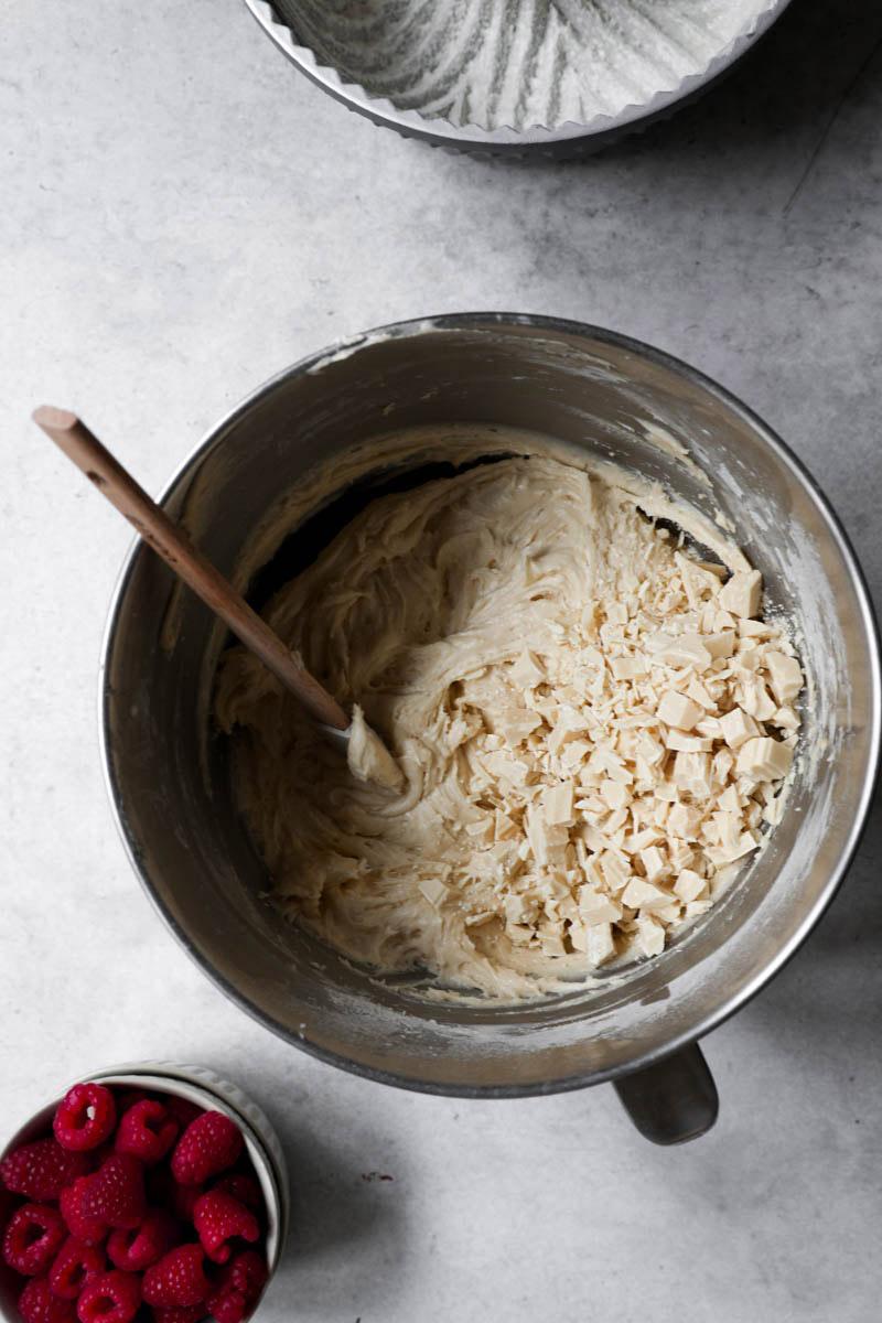 Un bol con la masa para el bizcocho más el chocolate blanco cortado y las frambuesas en bol al costado.