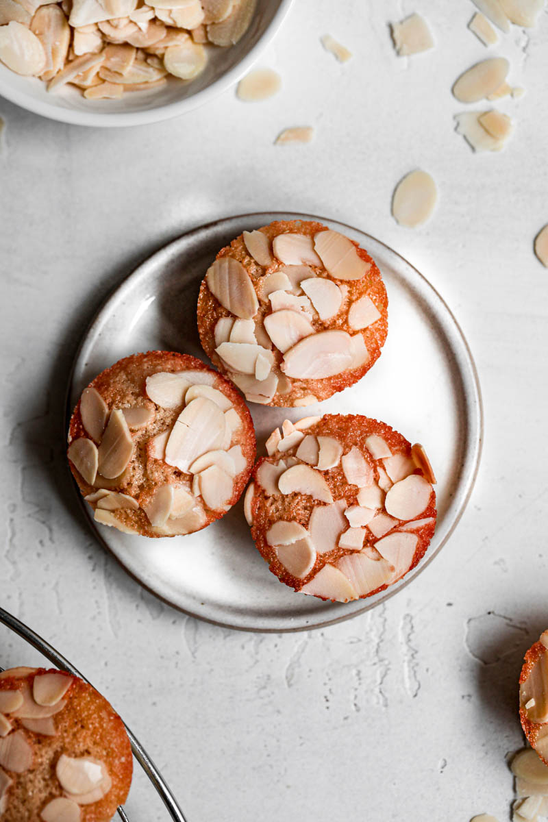 3 bizcochos de almendras sobre un plato pequeño blanco.