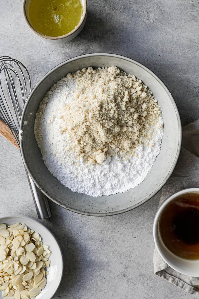 Los ingredientes secos dentro de un bol gris un plato lleno de almendras arriba del cuadro y claras de huevo dentro de un bol a su lado.