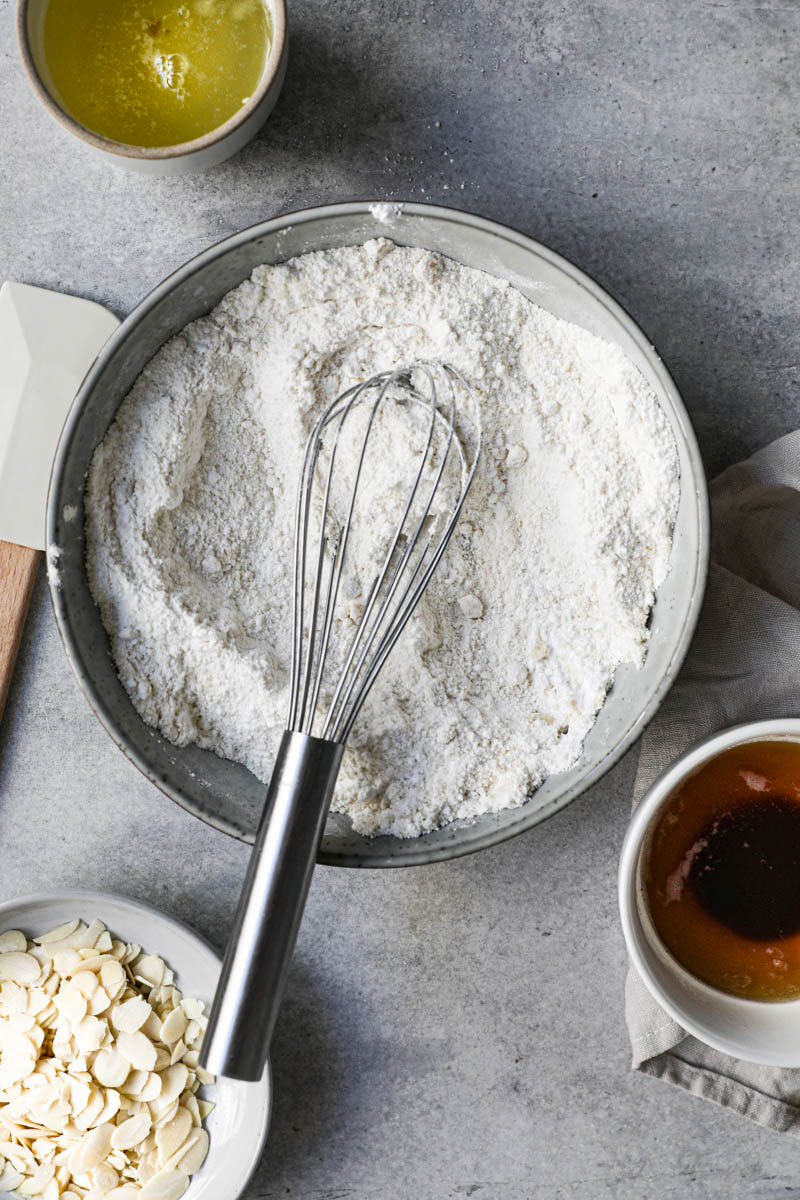 Los ingredientes secos mezclados dentro de un bol gris con un batidor dentro, un plato lleno de almendras arriba del cuadro y claras de huevo dentro de un bol a su lado.