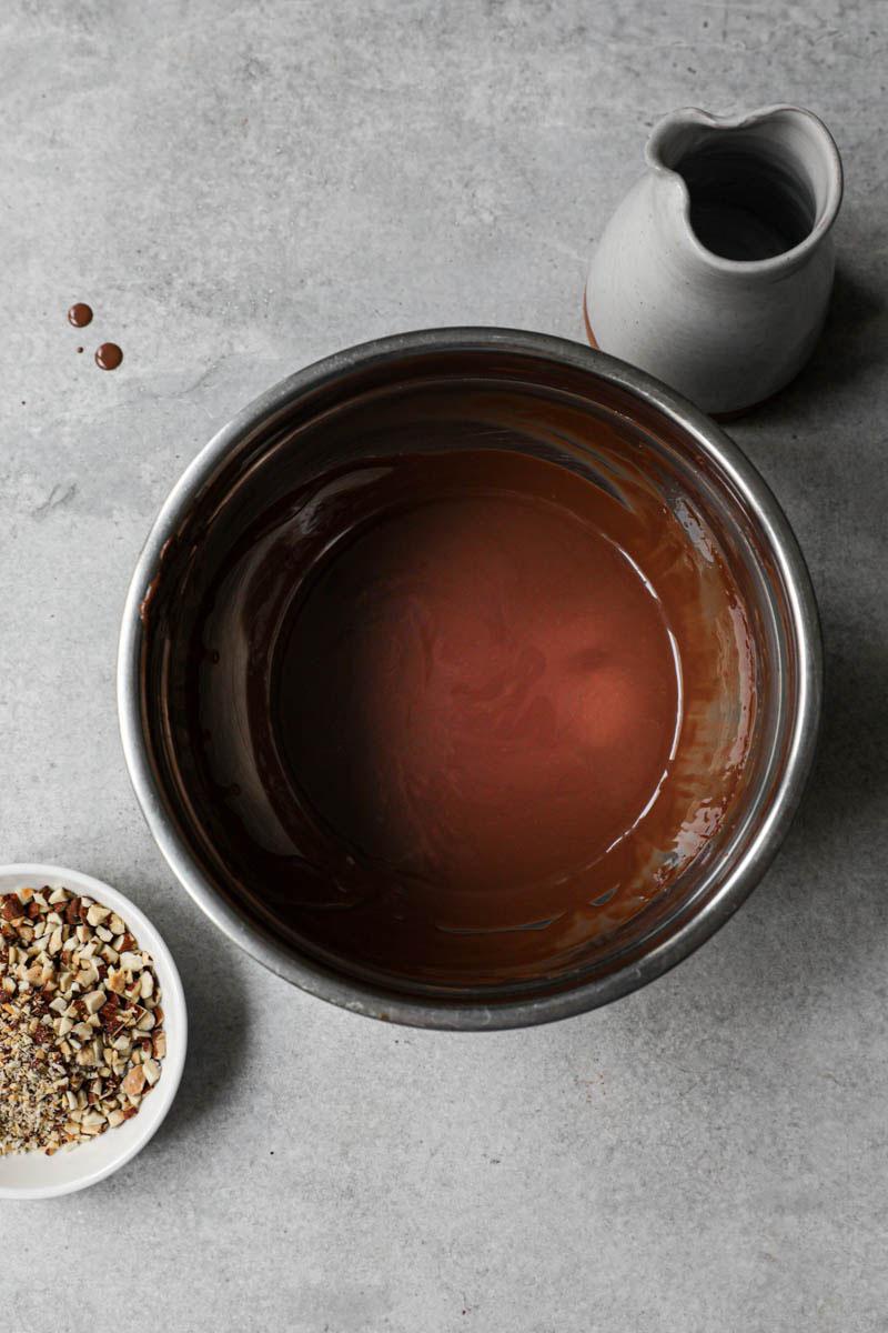 Un bol con chocolate derretido y aceite dentro con un pequeño recipiente con almendras tostadas a su lado