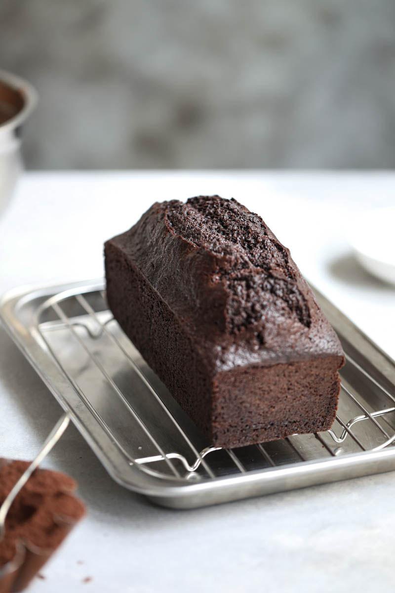 El bizcocho de chocolate horneado enfriándose sobre una rejilla con una jarrita gris por detrás
