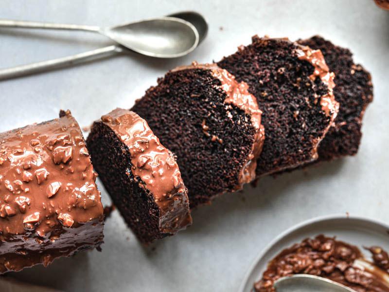 El bizcocho de chocolate húmedo glaseado cortado en porciones con dos cucharas arriba y, un plato por debajo.
