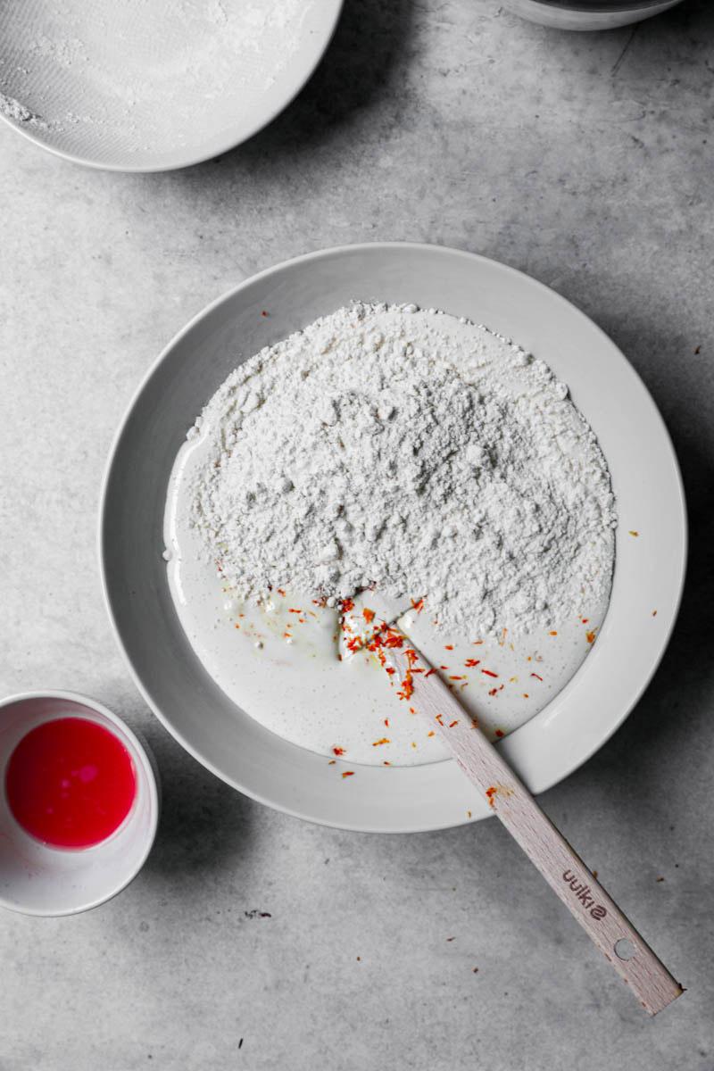 Huevos y azúcar blanqueados más la ralladura de naranja y la harina por encima.