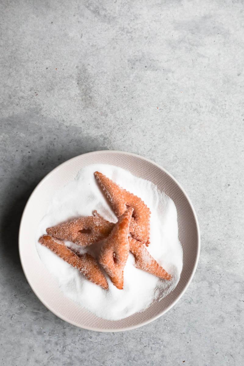 5 Buñuelos sobre un plato relleno de azúcar