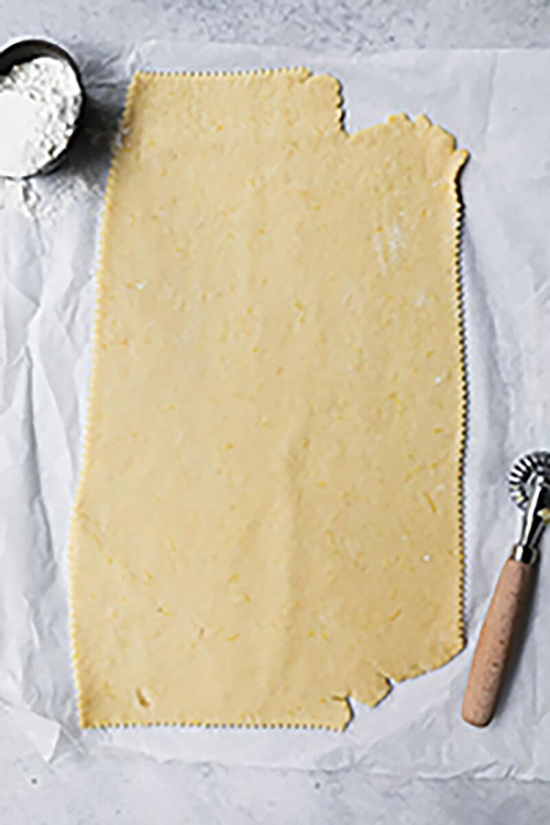 La masa de los buñuelos estirada sobre papel