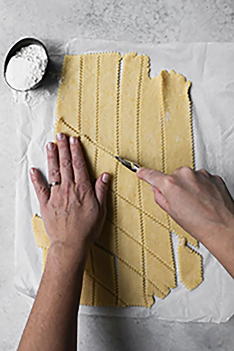 Una mano cortando los buñuelos con un cortador de pasta