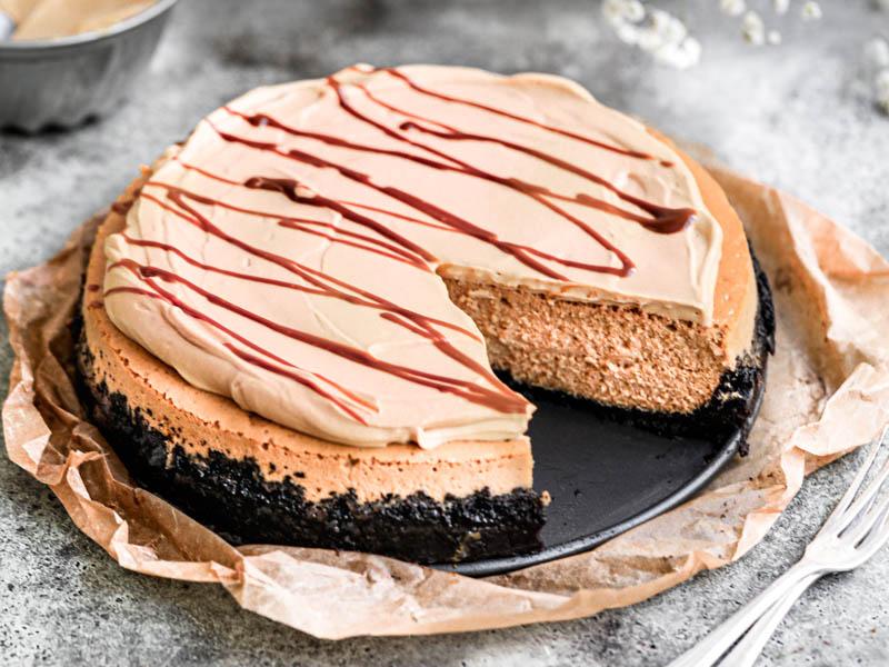 Primer plano del cheesecake de dulce de leche cortada viendo el interior sobre un plato negro colocado sobre un pedazo de papel vegetal marrón con algunas flores borrosas por detrás.