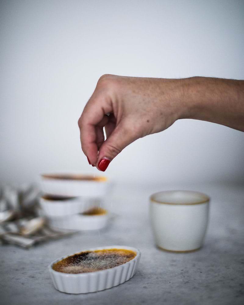 Espolvoreando azúcar sobre la creme brûlée