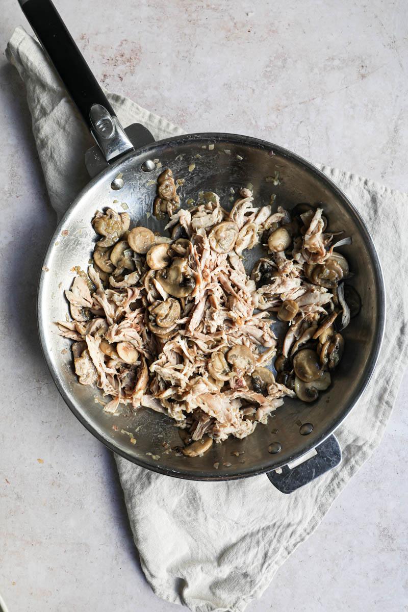 Una sartén sobre un lino beige, con los chalotes cocidos, los champiñones cortados cocidos y el pollo desmechado.