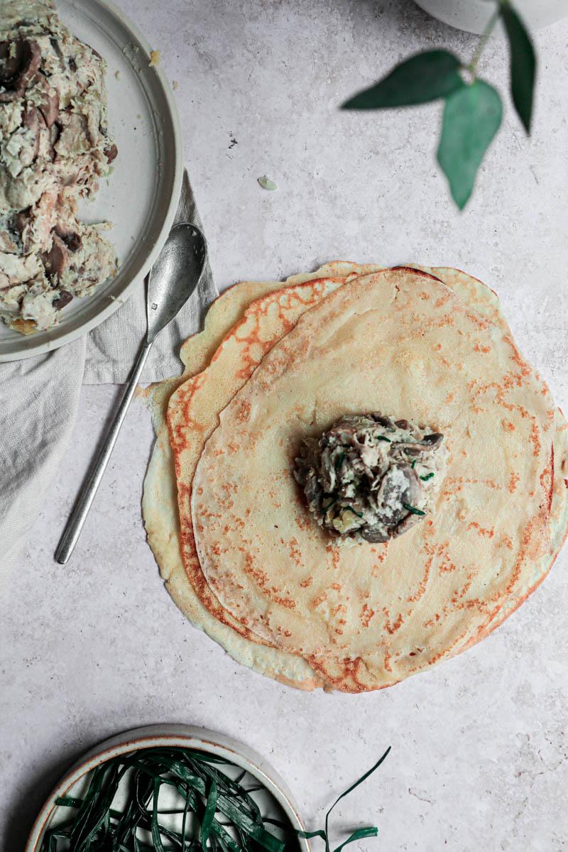Un crepe con una cuchara de relleno de pollo y champiñones en el centro, con un plato gris con el resto del relleno en el costado superior izquierdo y un plato pequeño con el cebollín blanqueado abajo.