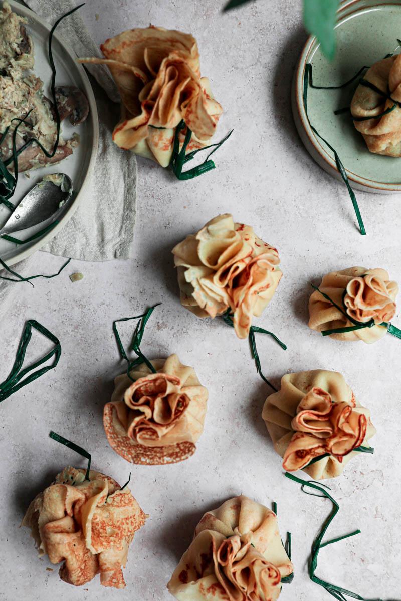 Muchos crepes doblados y cerrados con un cebollino, con un plato gris con el resto del relleno en el costado superior izquierdo y un plato pequeño con el cebollín blanqueado abajo, vistos desde arriba.