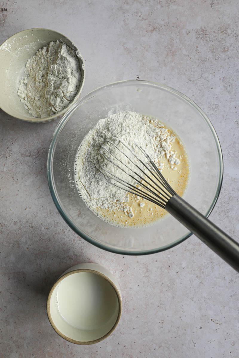 Un bol con la leche, huevos y la harina y un batidor dentro del bol, para realizar la masa de crepe.