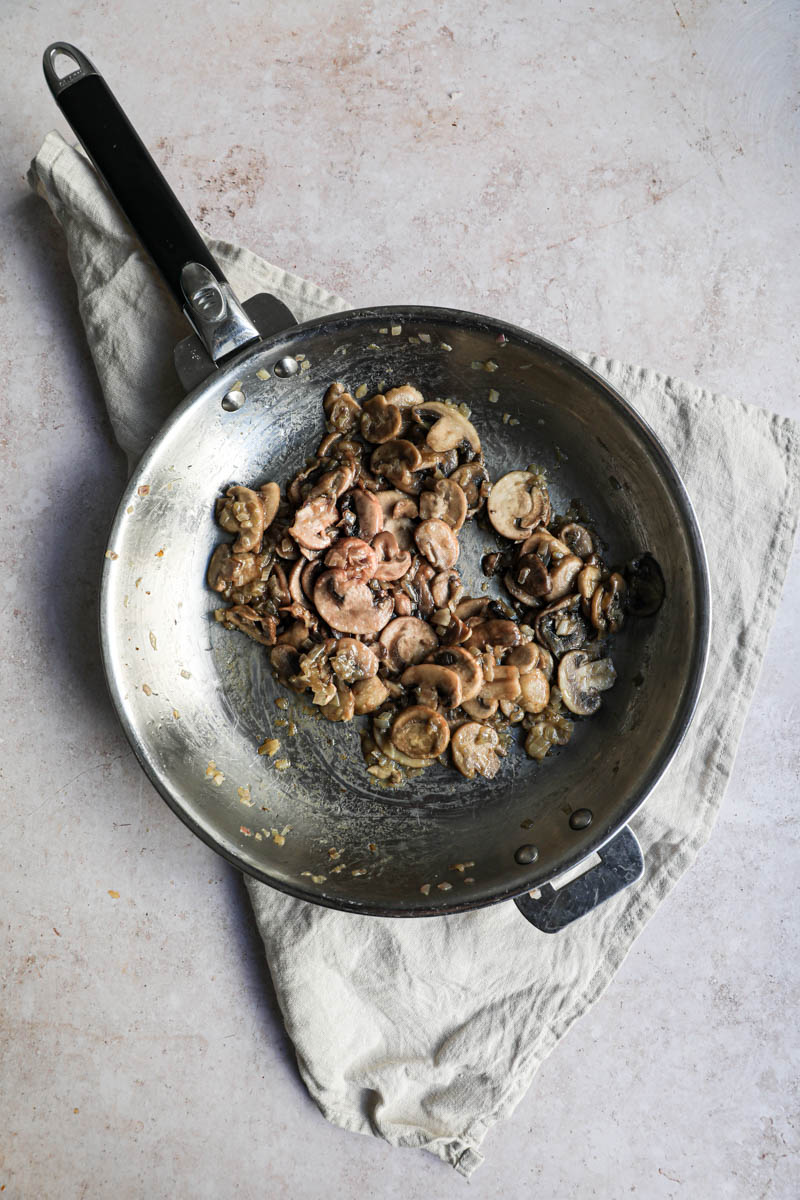 Una sartén sobre un lino beige, con los chalotes cocidos y los champiñones cortados cocidos.