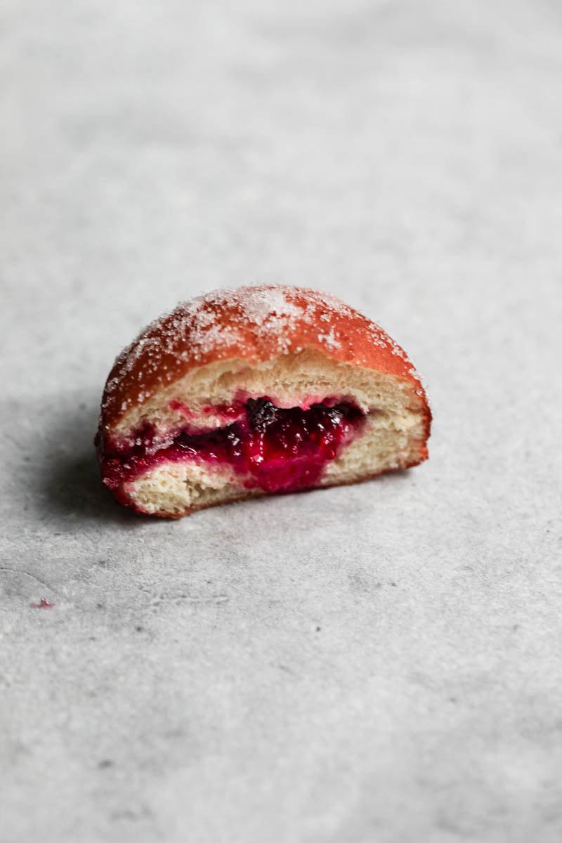 Un donut cortado al medio con la mermelada de frambuesa que sale y un pedacito de donut que se ve en el costado derecho.