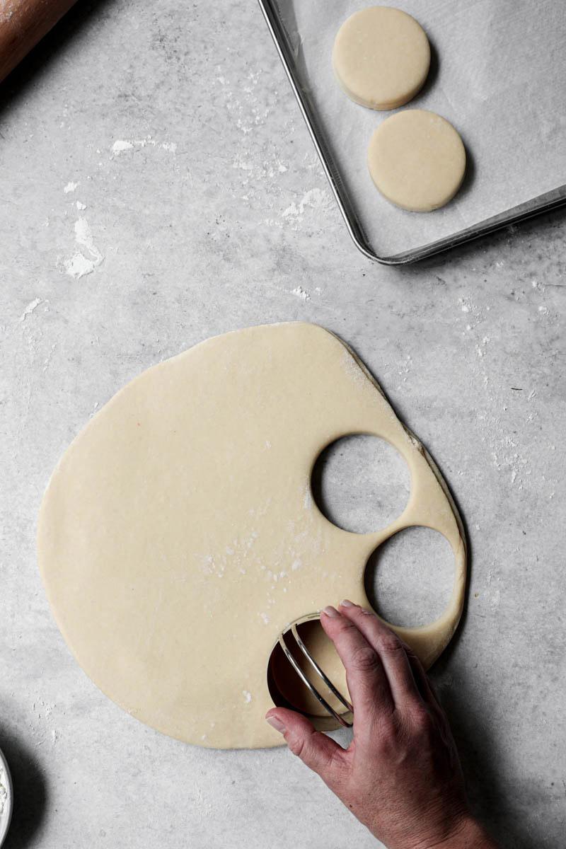 Una mano cortando los donuts con un cortador plateado.