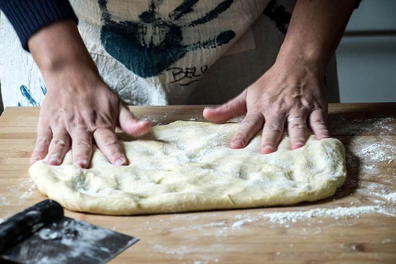 Dos manos aplastando la masa para retirar los gases sobre una plancha de madera