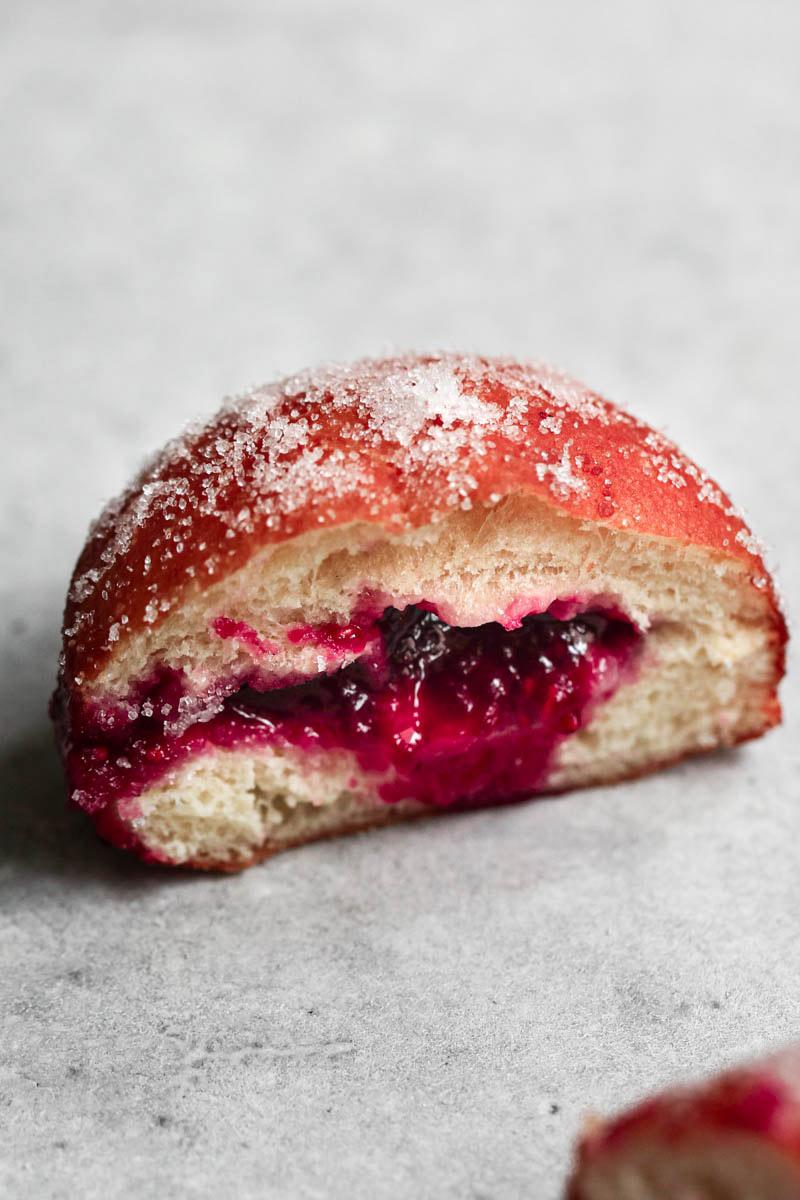 Primer plano de un donut cortado al medio con la mermelada que sale.