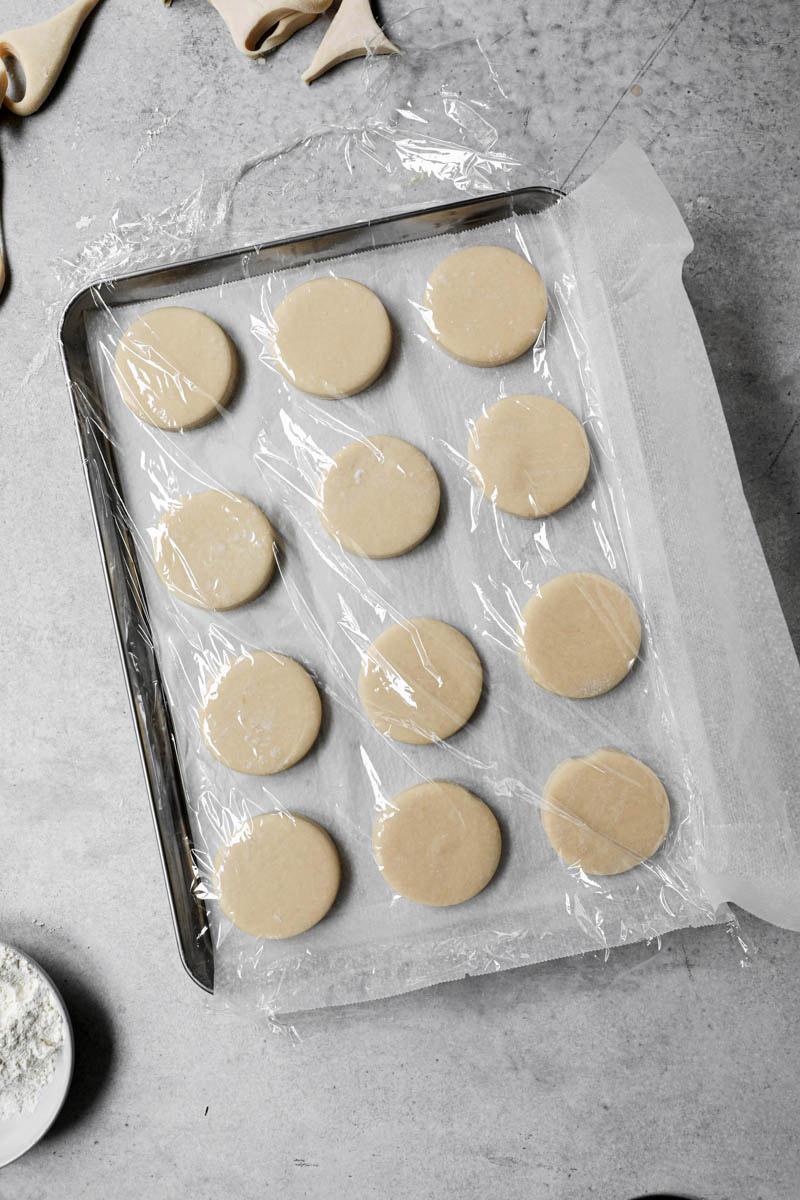 Los donuts cortados sobre una bandeja para horno forrada con papel manteca y cubiertas con papel film.
