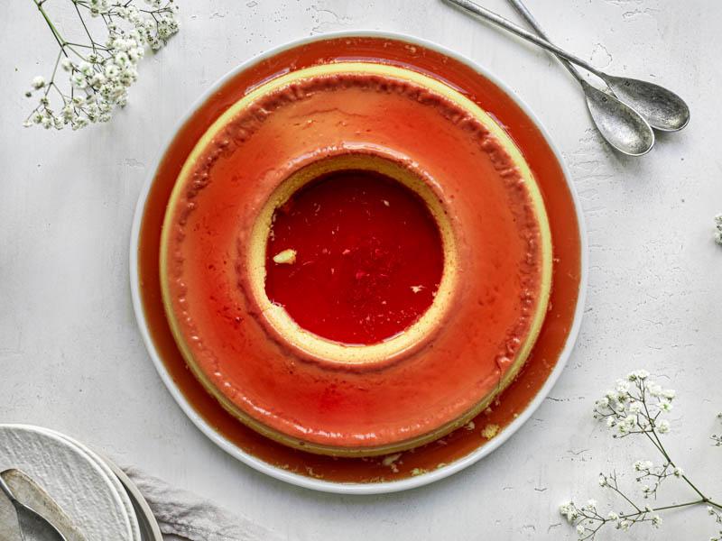 El flan casero entero visto desde arriba con dos cucharas pequeñas a su lado, algunas flores alrededor y unos platos blancos en el ángulo izquierdo del cuadro.