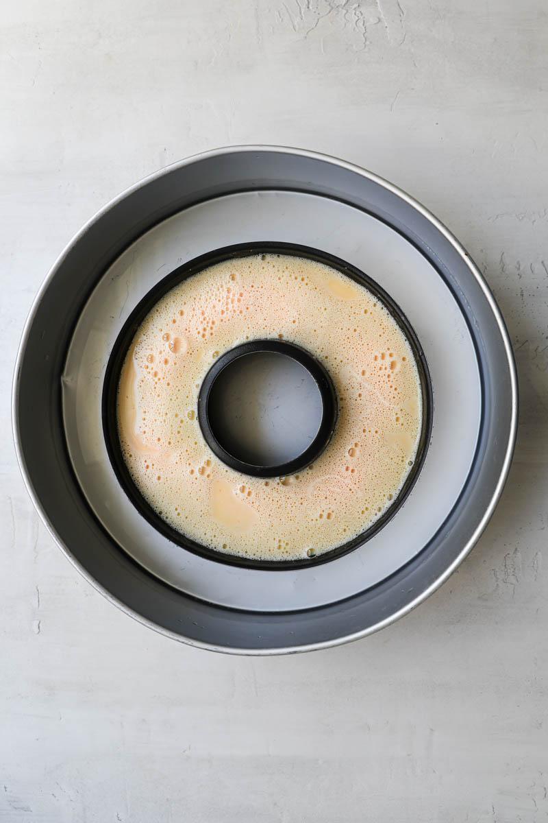 El molde del flan lleno dentro de una fuente para horno rellena con agua, listo para cocinar a baño maría.