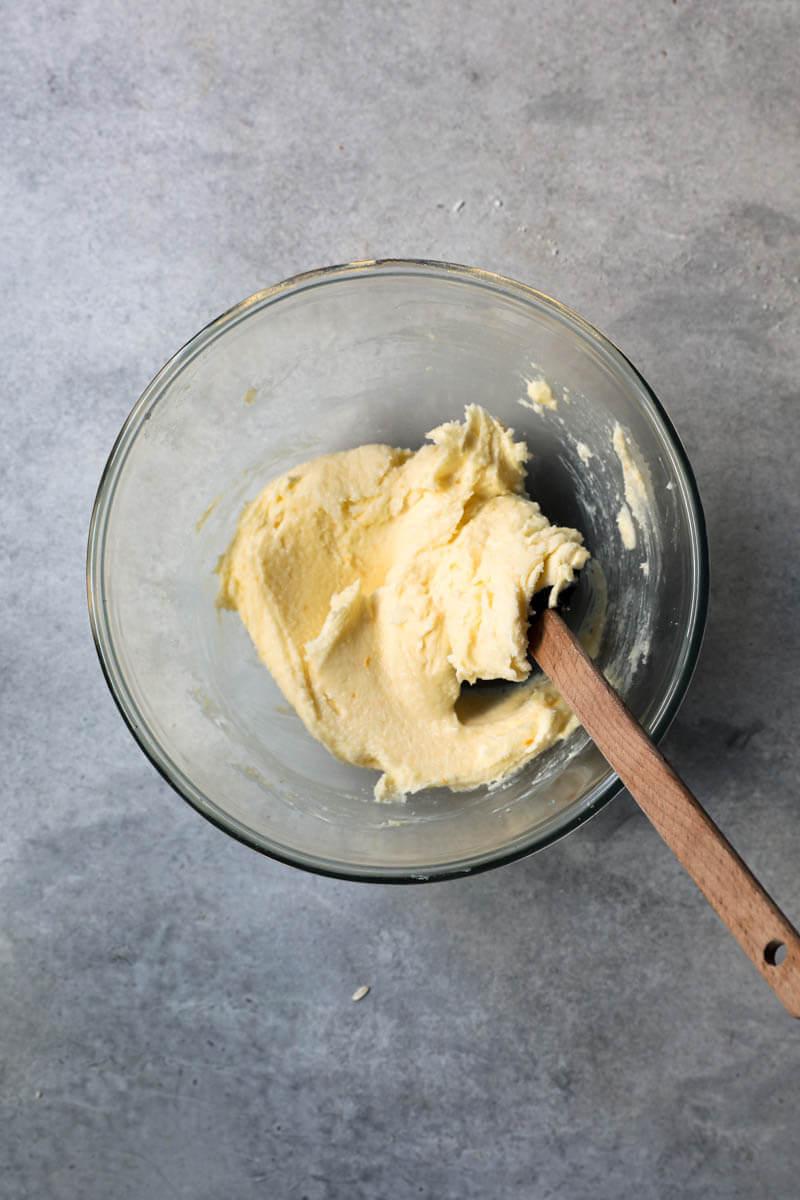 Manteca pomada, azúcar y ralladura de naranja mezclados en un bol