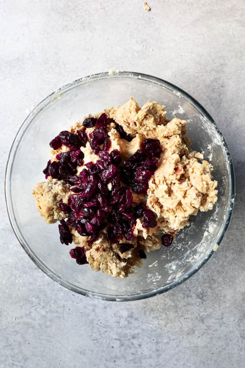 La masa de las galletas de avena y los arándanos rojos en un bol