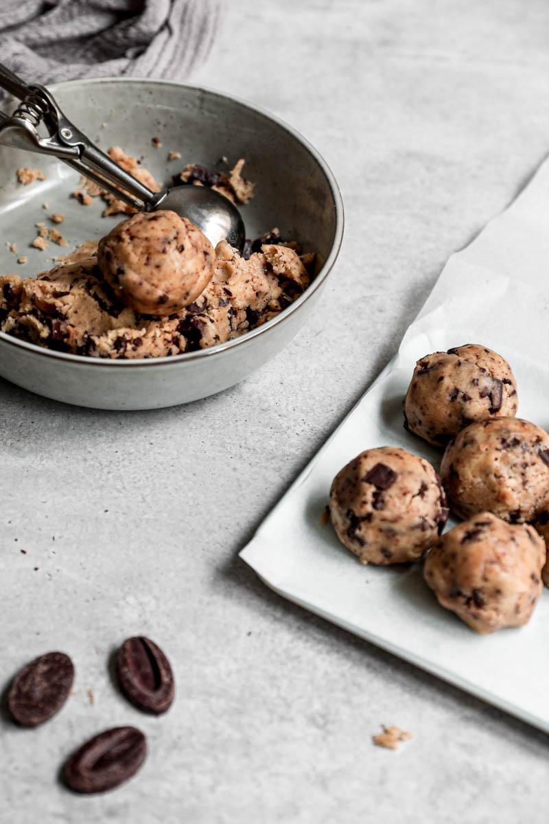 Plano de 45° de la masa de las galletitas en un bol y las bolas de galletas en una bandeja para horno