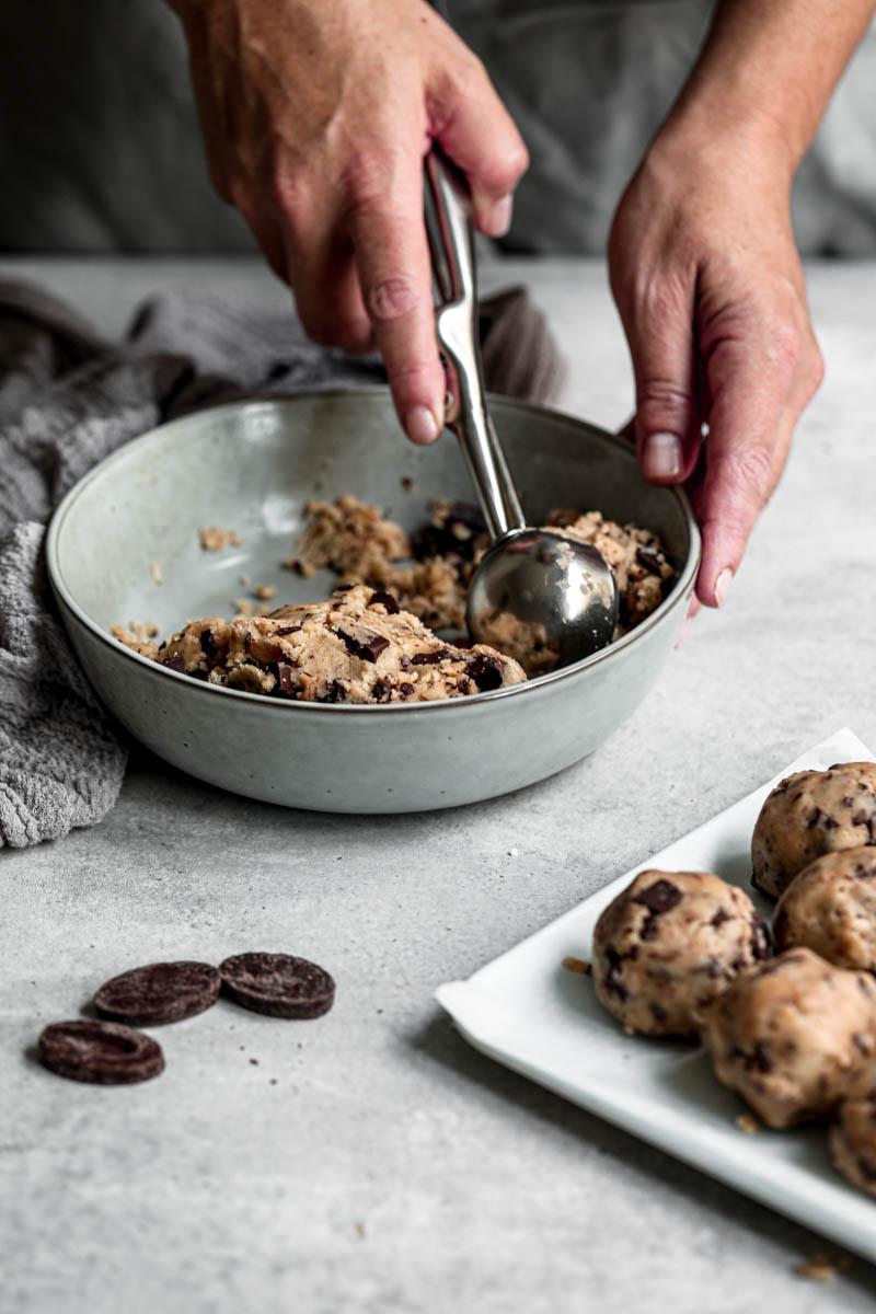 Plano de 45° de una mano haciendo las bolas de masa de cookies con una cuchara de helado