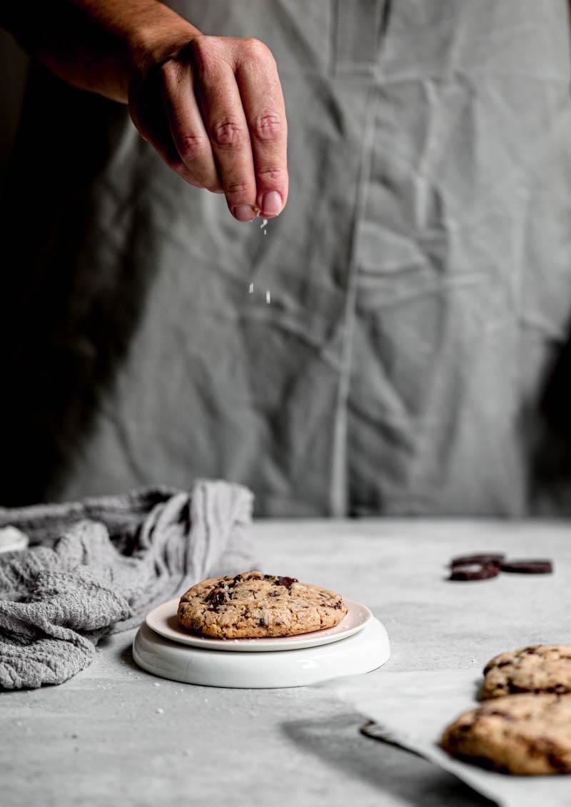 Una mano agregando una pizca de sal sobre las galletas con pepitas de chocolate