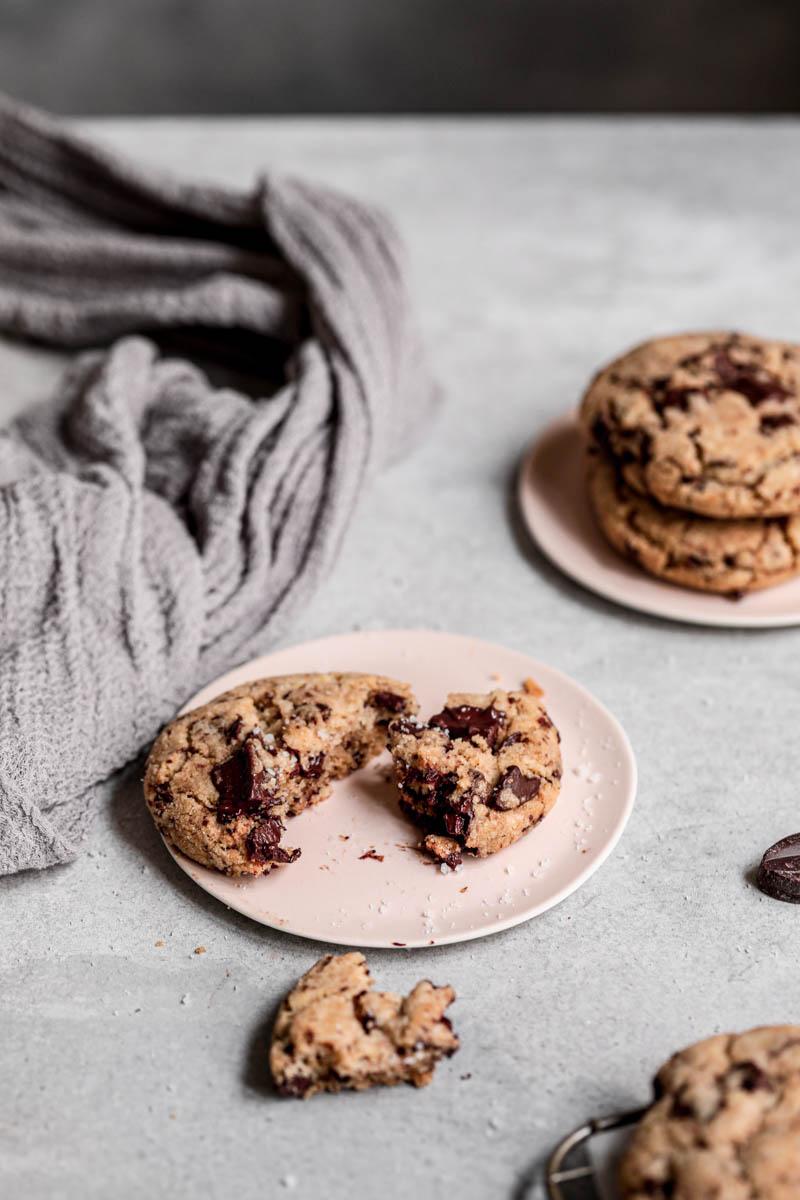 Plano de 45° de una cookie con pepitas de chocolate sobre un plato rosa