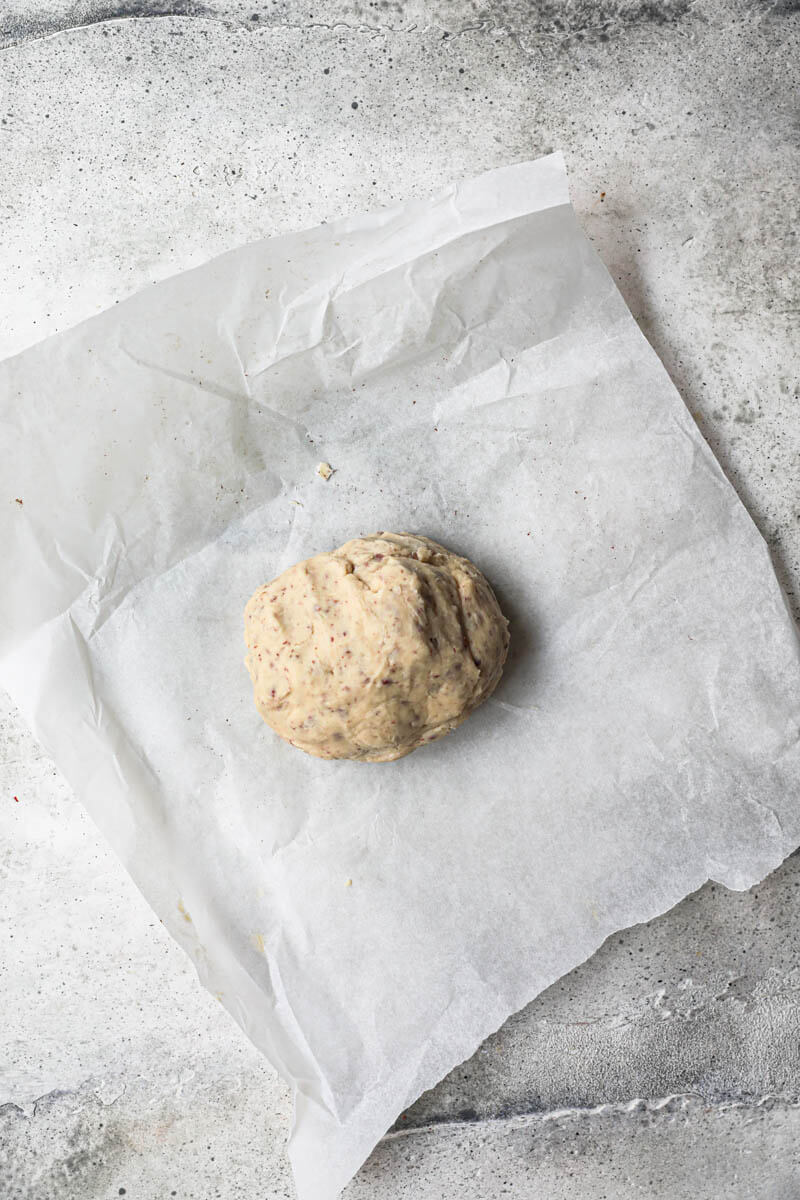 La masa de las galletas de nuez en forma de bola sobre papel vegetal