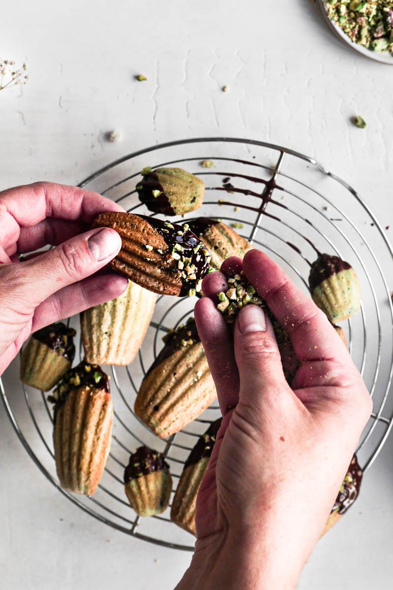 Una mano sosteniendo la magdalena glaseada y la otra cubriéndola con los pistachos triturados y una rejilla llena de magdalenas fuera de foco debajo.