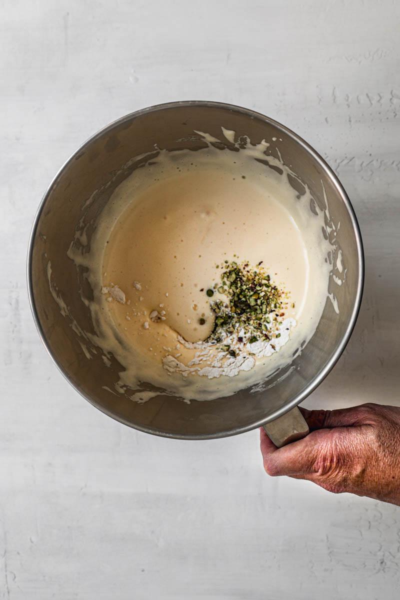 Un bol con los huevos y el azúcar blanqueados más los pistachos molidos y los ingredientes secos.