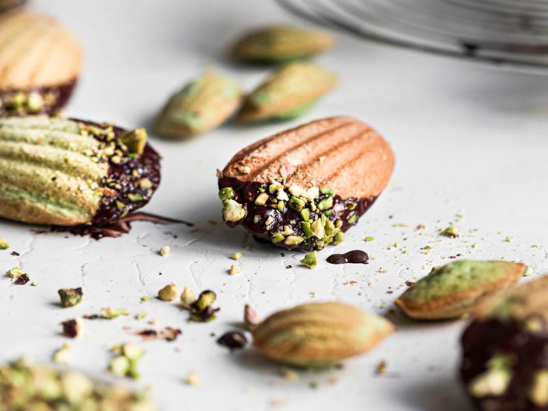 Una magdalena de pistacho cubierta con glaseado de chocolate en foco en el centro del cuadro con algunas magdalenas pequeñas alrededor.