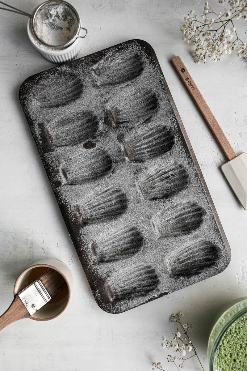 El molde de magdalenas enmantecado y enharinado con un pincel, y un colador pequeño alrededor.