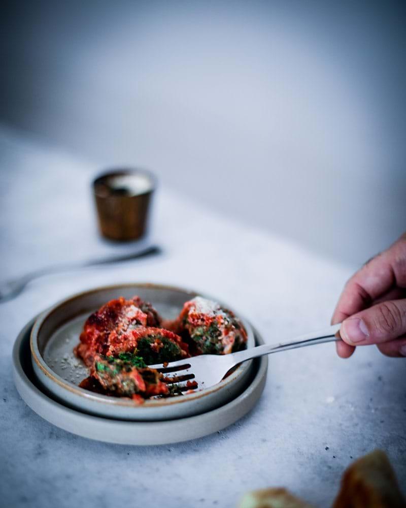 Plano de 45° de un tenedor cortando un malfati con salsa de tomate