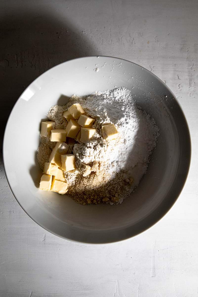 Plano aéreo de un bol con los ingredientes secos y la manteca cortada en cubos