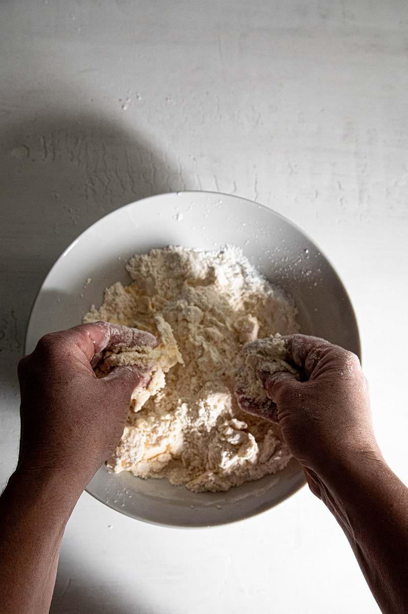 Plano aéreo de dos manos incorporando la manteca con la harina