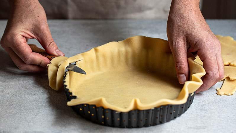 Plano de 90° de los manos cortando el excedente de masa con un cuchillo