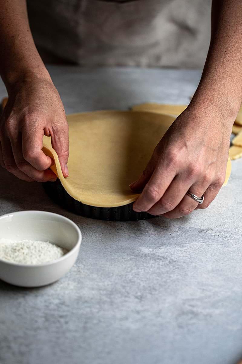 Plano de 45° de los manos forrando el molde para tarta dulce