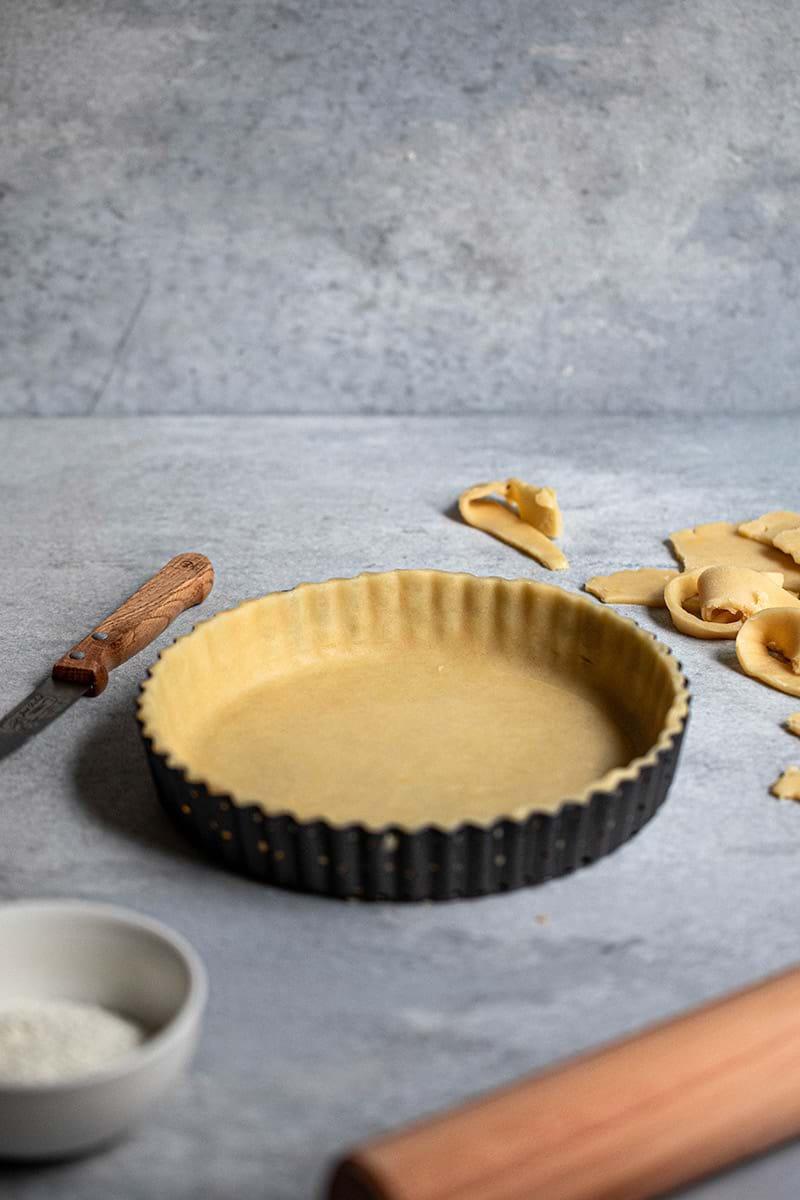 Plano de 45° del molde de tarta forrado con la masa sable con un palo de amasar al costado derecho