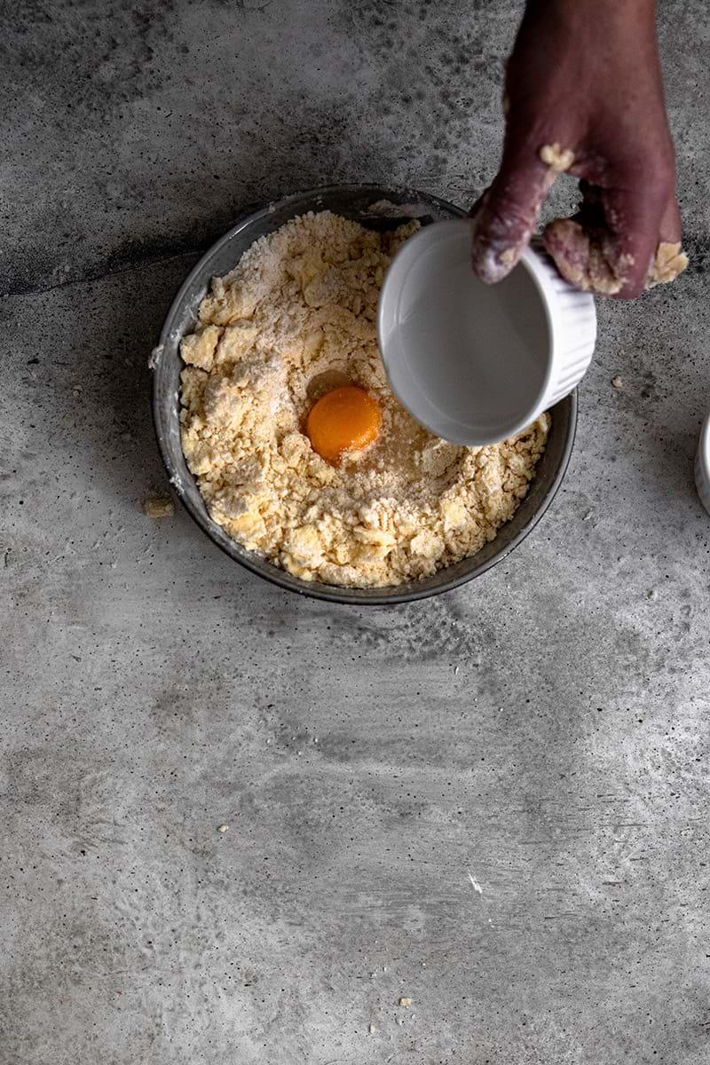 Plano aéreo de una mano agregando en huevo y el agua a la masa.