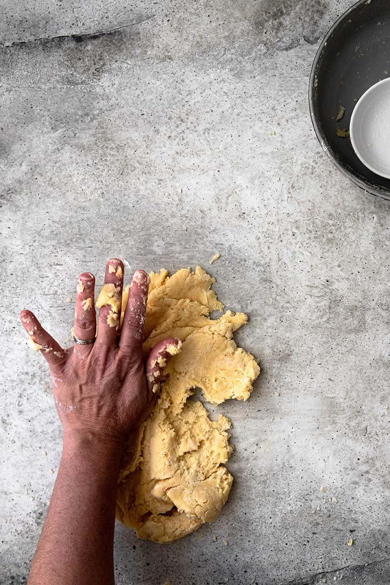 Plano aéreo de la masa para tarta sobre la mesada y una mano haciendo el fressage.
