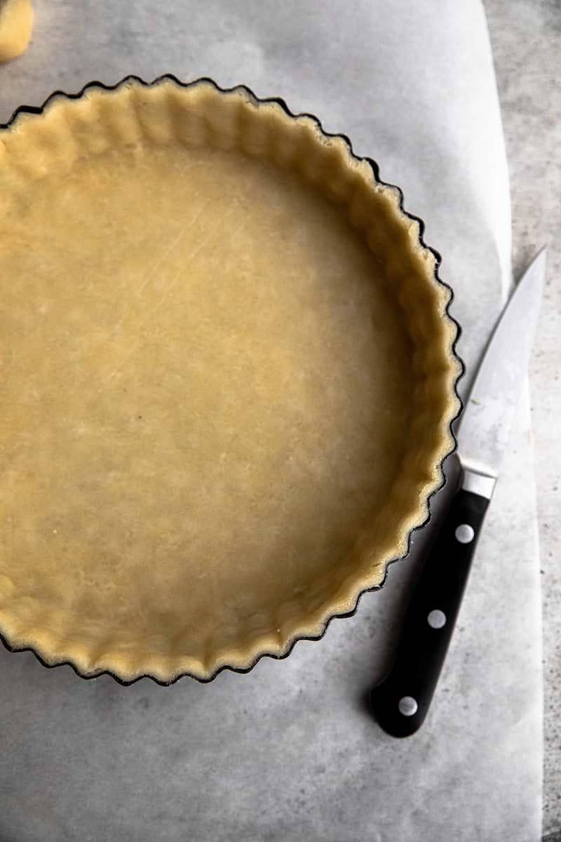Plano aéreo de la masa para tarta en el molde con un cuchillo a la derecha.